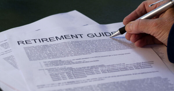 'Retirement Guide' written on a stack of papers with a human hand holding a pen – meant to represent a retirement planning resource guide