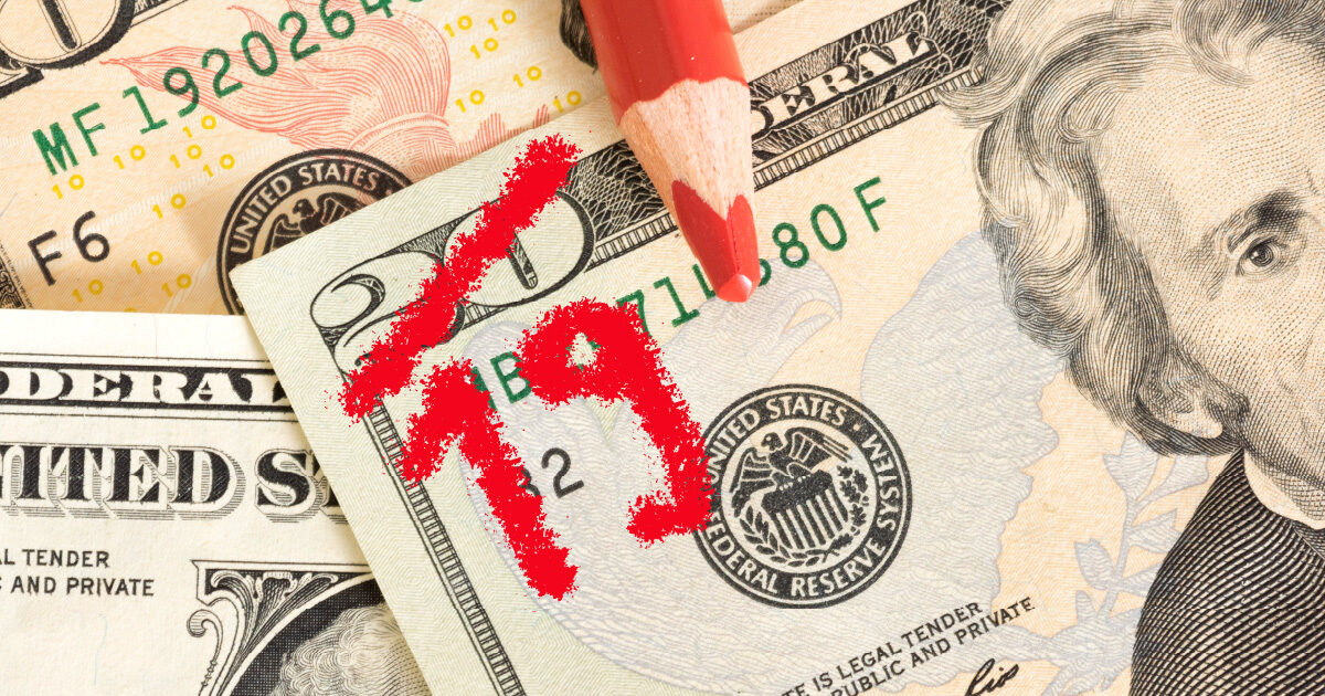 A twenty-dollar bill has the number 20 scratched out in red and replaced with a 19 to indicate the loss of purchasing power associated with inflation.