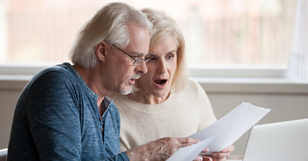 A couple with shocked expressions is reviewing their Medicare forms. Their expression indicates a costly mistake was made.