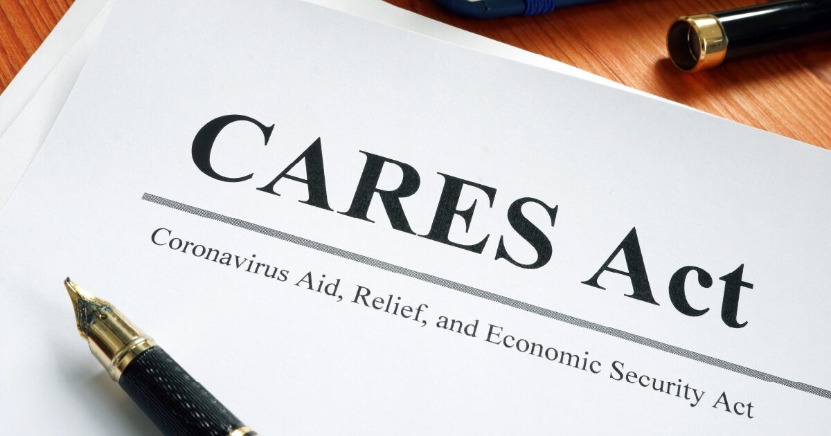 A paper report with CARES Act – Coronavirus Aid, Relief, and Economic Security Act written on it, with an open ink pen lying on top – indicating Partial Plan Termination Rules were clarified by the CARES Act.