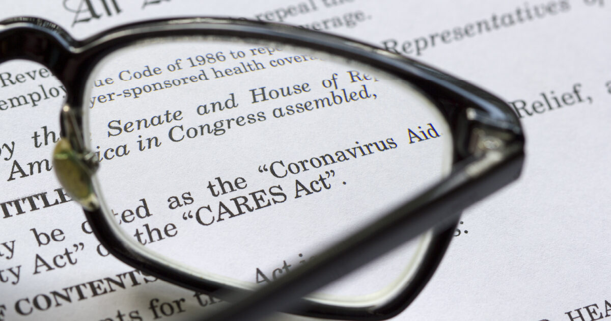 "A pair of glasses lying on a page that reads ""CARES Act"" and ""Coronavirus"" signifying that retirement planners should consider new changes to the CARES Act"