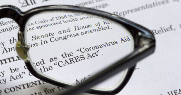 """A pair of glasses lying on a page that reads """"CARES Act"""" and """"Coronavirus"""" signifying that retirement planners should consider new changes to the CARES Act"""