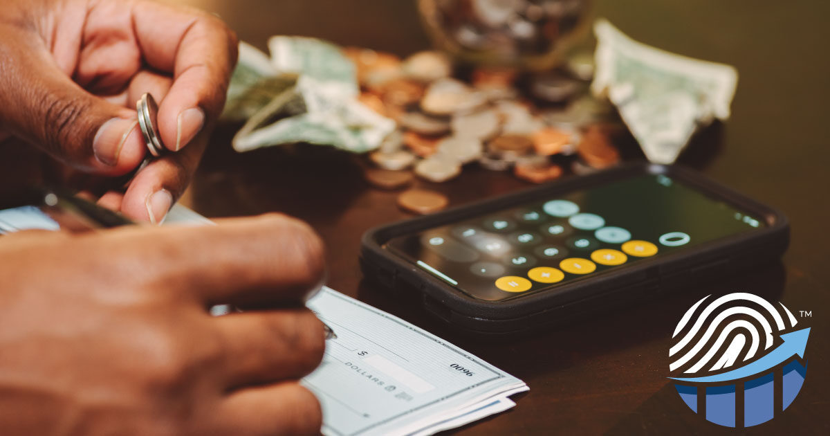 A person is writing a check and counting money with a calculator. The FINANCIAL FINGERPRINT™ logo by Meld Financial is present in the bottom right-hand corner.