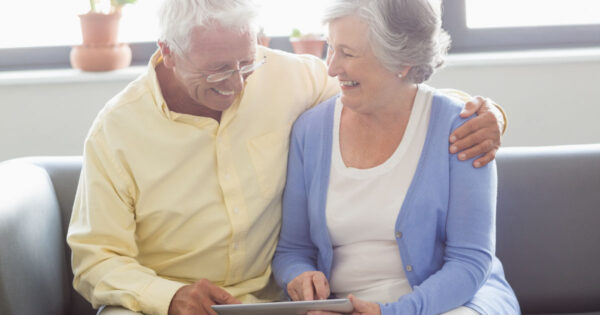 Senior couple studying 2021 changes to Medicare premiums, deductibles and coinsurance on a mobile device
