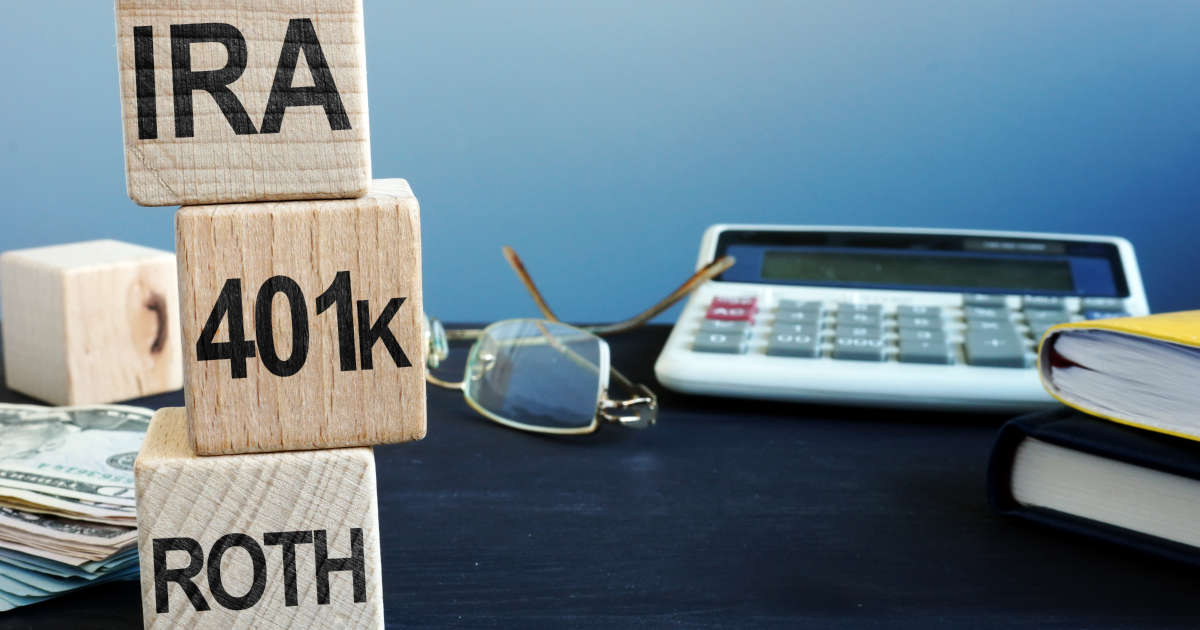 A desk with a calculator, glasses, money and 3 blocks with IRA, 401k and ROTH written on them. These are meant to represent a guide to the many different kinds of retirement plans.