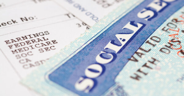 Social security card lying on top of a pay stub listing payroll taxes such as Medicare and Social Security – indicating changes to Social Security Benefits due to COVID-19